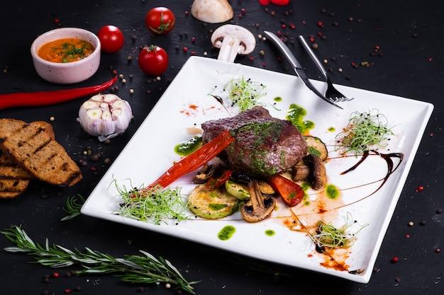 Филе миньона из телятины с овощами гриль. на темной поверхности
