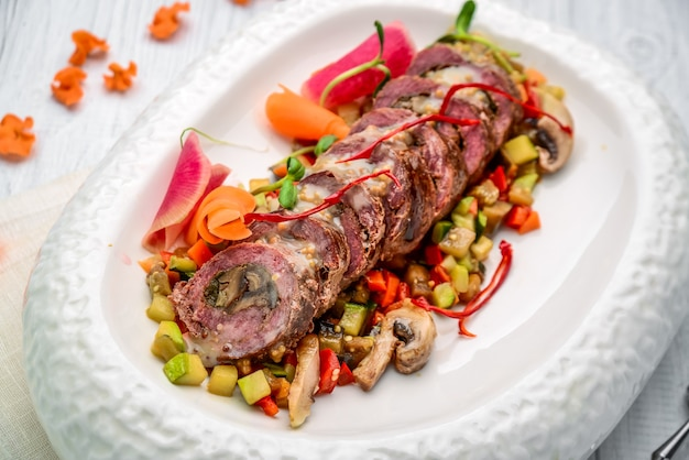 Veal roll stuffed with mushrooms with vegetable stew. on the wooden table