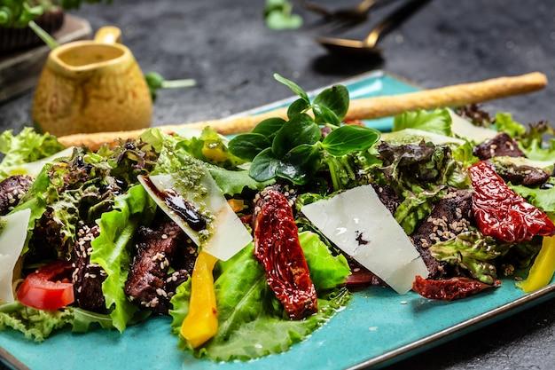青いプレートにレタス、パルメザンチーズ、サンドライトマトを添えた子牛のサラダ。レストランの食べ物、クローズアップ。肉サラダ。食品レシピの背景。閉じる。