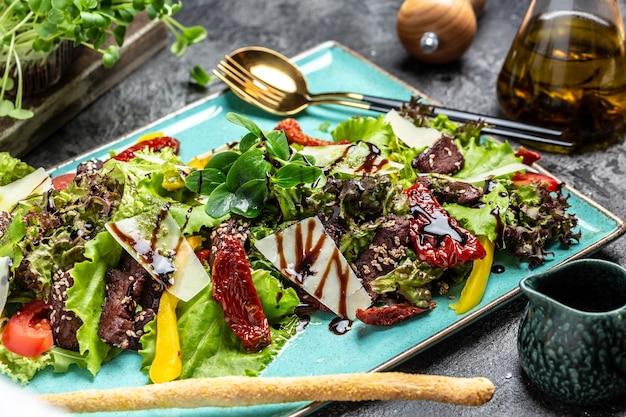 レタス、パルメザンチーズ、サンドライトマトの子牛のサラダ。レストラン料理、ミートサラダ。食品レシピの背景。閉じる。