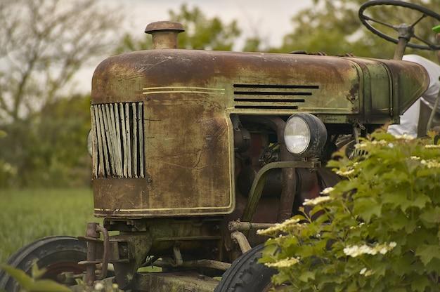 Vecchio trattore vintage usurato e con i segni del tempo in un campo pronto per un'altra dura giornata di lavoro