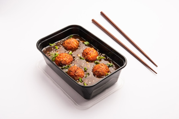 Veg manchurianは、オンライン食品配達注文用に黒いプラスチック容器に詰められています。人気のインド風中華レシピ
