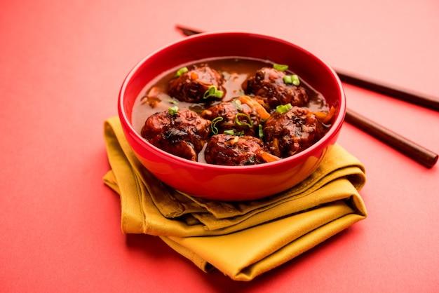 그레이비를 곁들인 야채 또는 닭고기 만주 - 젓가락으로 그릇에 제공되는 인도의 인기 있는 음식