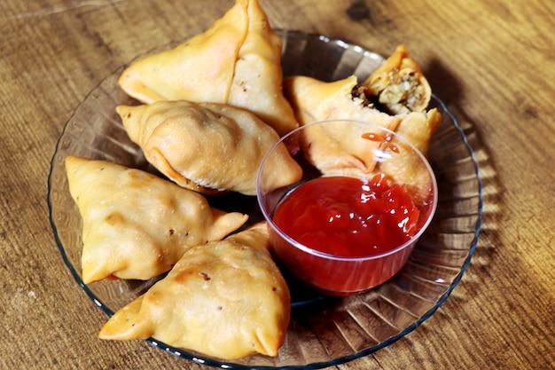 ベジサモサ-クリスピーでスパイシーなインドの三角形のスナックで、マイダ粉の外層がカリカリになっていて、マッシュポテト、エンドウ豆、スパイスが入っています。