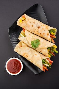 Овощной спринг-ролл или обертка, также известная как фрэнки, сделанная с использованием панир и овощей, фаршированных внутри чапати или роти. подается с томатным кетчупом. выборочный фокус