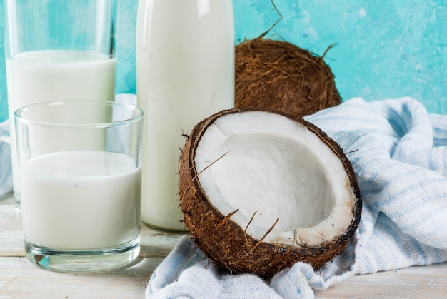 Vegan alternative food, coconut non-dairy milk on light blue background, copy space