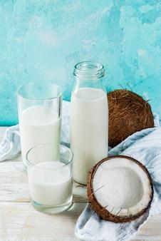 ビーガンの代替食品、明るい青の背景、コピースペースにココナッツ非乳製品ミルク Premium写真