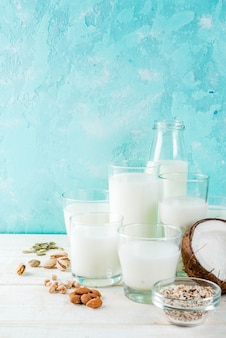 ビーガンの代替食品、さまざまな非乳牛乳ご飯、ココナッツ、アーモンド、ピスタチオ、ゴマ、カボチャの種、大豆、ナッツ、オートミール、ライトブルー、