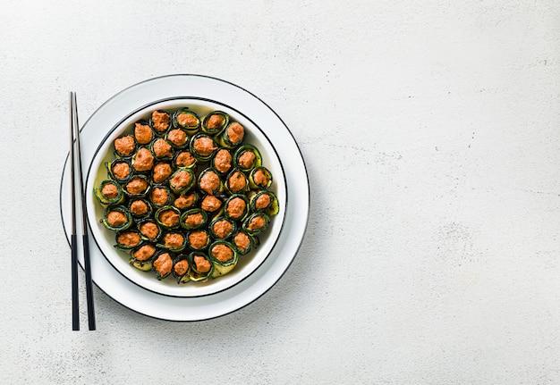Веганская закуска из грузинской кухни. мягкая смесь жареного болгарского перца и грецких орехов с пряными специями, завернутая в жареные листья цуккини здоровая кухня.