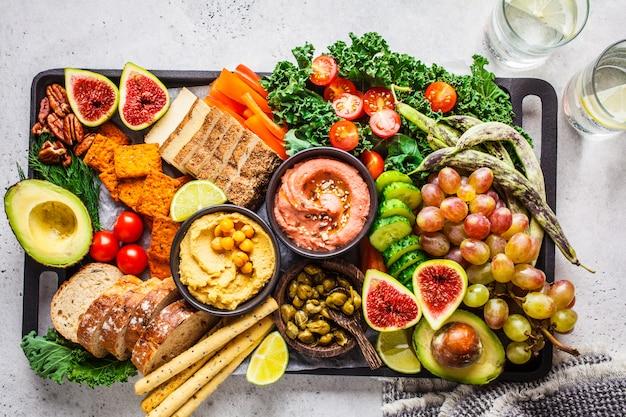 Vegan appetizer platter, hummus, tofu, vegetables, fruits and bread ,