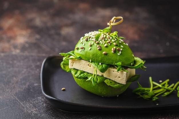 Бургер тофу авокадоа vegan на черном блюде. здоровая пища детоксикации, концепция еды основанная заводом.