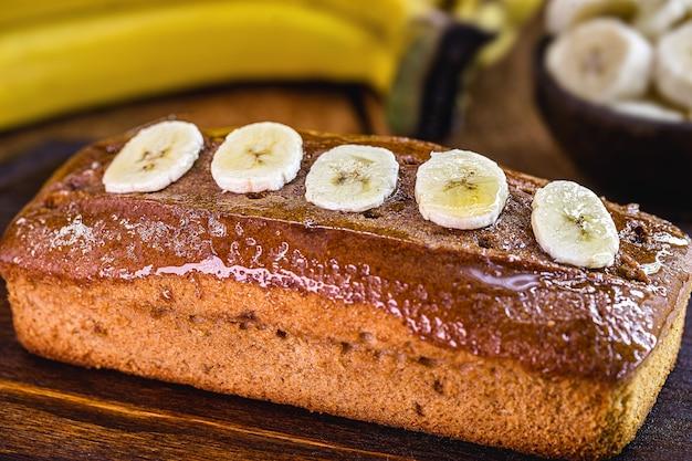オーツ麦、キノア、グルテンフリーの小麦粉で作られたビーガンバナナブレッド、その周りに果物があります