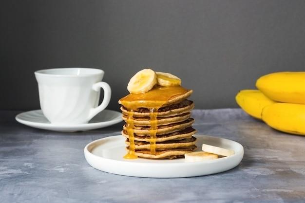 ビーガンバナナのパンケーキはバナナと蜂蜜と白いプレートに積み重ねられます