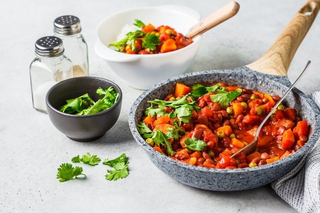 Vegan bean stew with tomatoes and rice in a pan