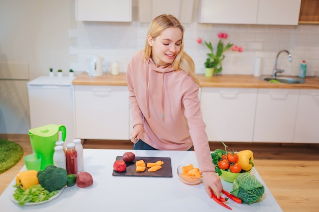 Vegan beautiful blonde woman cooking raw colorful vegetables in the kitchen. raw food diet. vegetarian food. healthy eating