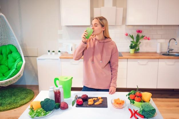 ビーガンの美しい金髪女性がキッチンで生野菜を調理しながらデトックス水を飲む