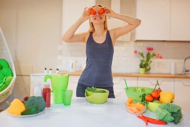 Веганская красивая белокурая женщина развлекается с органическими красными помидорами, готовя сырые красочные овощи на белой кухне. сыроедение. вегетарианская пища. здоровое питание