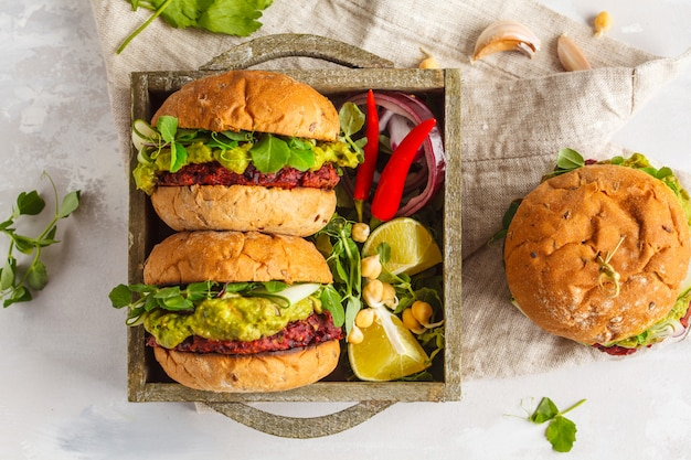 Vegan beet chickpea burgers with vegetables, guacamole and rye buns in wooden box. healthy vegan food concept. top view, copy space