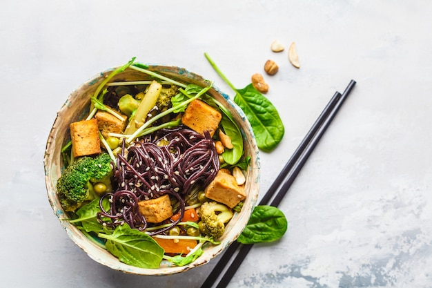 Vegan black rice noodles with tofu and vegetables, white background.