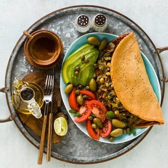 버섯과 부추를 곁들인 글루텐 프리 계란이없는 병아리 콩 오믈렛의 완전 채식 아침 식사. 그리고 잘 익은 신선한 토마토, 아보카도, 올리브 및 케이 퍼 샐러드.
