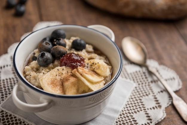 Веганский завтрак, каша с овсяными хлопьями, банан, черника, чиа, корица, кленовый сироп и клубничное варенье на деревянный стол.