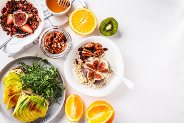 Веганский завтрак стол с тостами авокадо, овсянка, фрукты, на белом
