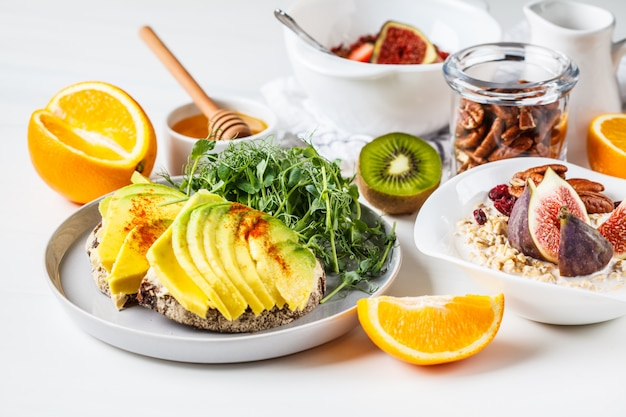 Vegan breakfast table with avocado toast, oatmeal, fruit, on white