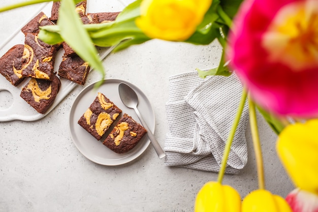 Vegan brownie with peanut butter on white background, top view. spring food flat lay.