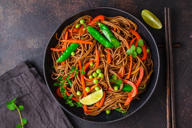 Vegan buckwheat soba noodles with vegetables in black plate , top view.