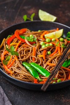Vegan buckwheat soba noodles with vegetables in black plate .
