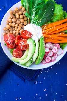 Vegan buddha bowl on blue wooden . bowl with carrot, lettuce, tomatoes cherry, radish, avocado and chickpea. vegetarian, healthy, detox food . top view.