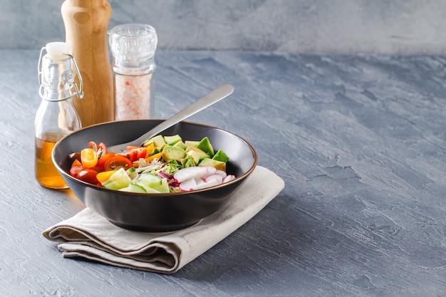 Веганская чаша будды. чаша со свежими сырыми овощами - помидорами черри, огурцами, редисом, авокадо, салатом романо, фриссе и ридичо. здоровый вегетарианский салат. кетогенная диета.