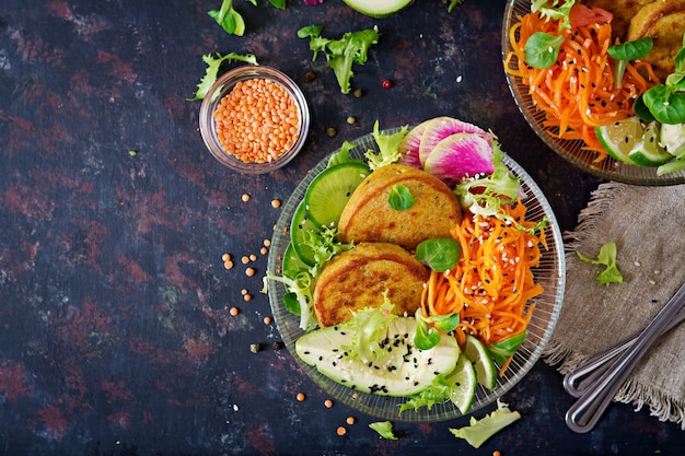 Vegan buddha bowl dinner food table. healthy food. healthy vegan lunch bowl. fritter with lentils and radish, avocado, carrot salad. flat lay. top view