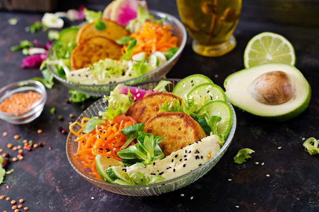 Vegan buddha bowl dinner food table. healthy food. healthy vegan lunch bowl. fritter with lentils and radish, avocado, carrot salad.