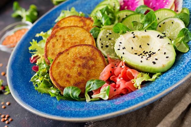 Vegan buddha bowl dinner food table. healthy food. healthy vegan lunch bowl. fritter with lentils and radish, avocado salad