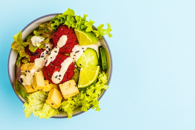 Vegan buddha bowl with beetroot meatballs, vegetables, tahini dressing and baked tofu. blue background, top view, copy space. healthy vegan food concept.