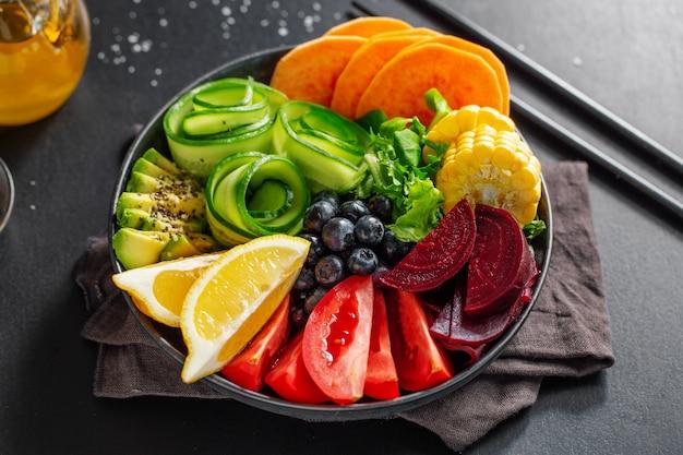 灰色の背景のボウルに野菜や果物を添えたビーガンブッダボウル。閉じる