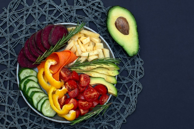 Vegan, buddha detox bowl recipe with avocado, carrot, cucumber, beet, yellow pepper