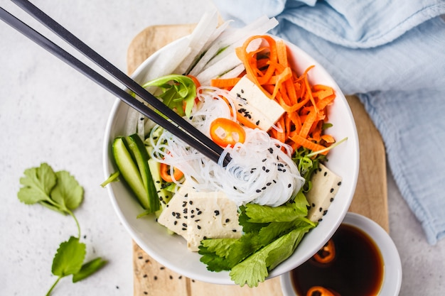 Vegan bun cha salad bowl. vietnamese rice noodle with tofu and chilli vegetables salad in white bowl