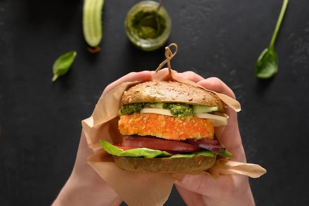 緑のスピルリナパン野菜ビーガンチーズペストニンジンミートボールのビーガンバーガーを手に