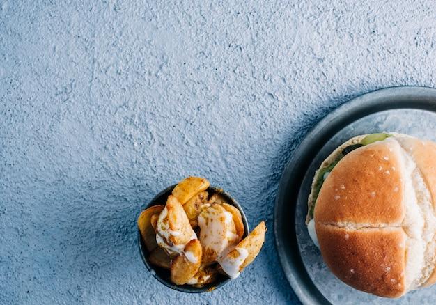 블루 테이블 배경에 금속 그릇에 향신료와 소스와 감자 튀김과 채식 버거