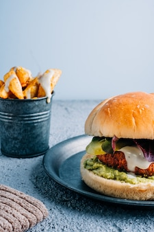 Vegan burger with sauce and guacamole on metal plate with french fries with spices