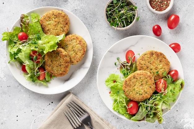 Веганские гамбургеры с киноа, брокколи и салатом в тарелках на светлом мраморном фоне
