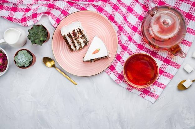 ガラスのティーポットと一杯のお茶、スプーン、乾燥したバラのつぼみ、砂糖の立方体、お茶の時間の概念、flatlay、セメントの背景とビーガンキャロットケーキの作品