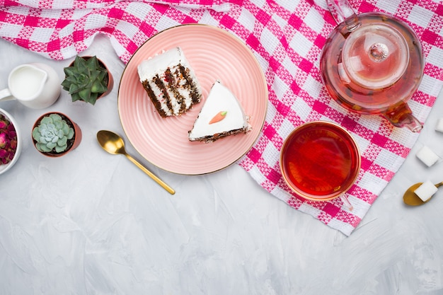 Vegan carrot cake pieces with glass teapot and cup of tea, spoons, dried rose buds and sugar cubes, tea time concept, flatlay, cement background