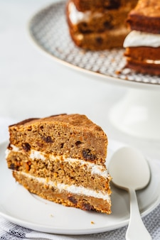 Vegan carrot cake with coconut cream, white background.