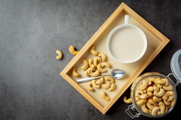Vegan cashew milk in glass with cashews nuts on dark background