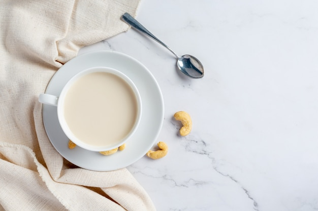 Vegan cashew milk in glass with cashews nuts on marble background