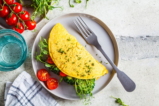 Vegan chickpea omelet with broccoli, tomatoes and seedlings, top view. healthy vegan food concept.