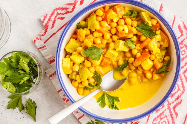 Vegan chickpea vegetables with coconut milk and cilantro, top view.